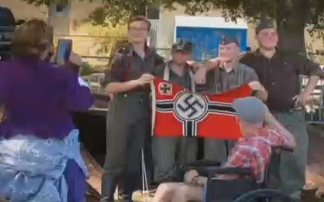 Des hommes participant à un festival culturel dans le Michigan et qui avaient reconstitué des scènes de la Deuxième guerre mondiale ont suscité l'indignation après avoir posé avec un drapeau nazi pour une photo devenue virale sur  Facebook , le 24 septembre 2017 (Capture d'écran)
