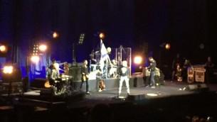 Chrissie Hynde brandit un grand drapeau israélien au début du concert du groupe The Pretenders à Tel Aviv, le 23 septembre 2017 (Crédit : Equipe du Times of Israel)