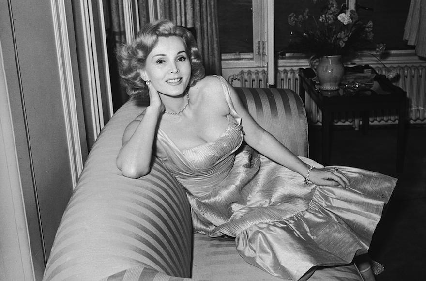 L'actrice hongroise Zsa Zsa Gabor sur un sofa dans une robe du soir froncée en 1952. (Crédit : Nixon/Express/Getty Images/JTA)