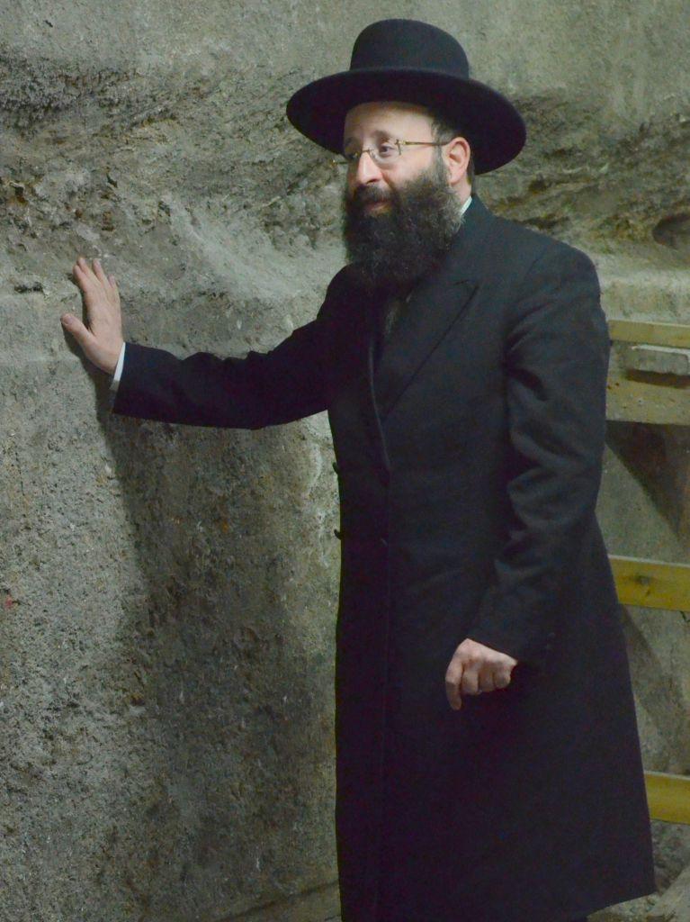 Le rabbin Shmuel Rabinovitch, rabbin du mur Occidental et des lieux saints, devant les pierres du mur Occidental découvertes pendant les fouilles sous l'Arche de Wilson, dans la Vieille Ville de Jérusalem, en octobre 2017. (Crédit : Yaniv Berman/Autorité israélienne des Antiquités)