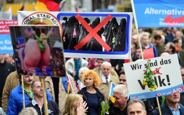 Un partisan du parti populiste de droite de l'Alternative pour l'Allemagne (AfD) porte une pancarte montrant des femmes en niqab barrées d'une croix durant une manifestation contre la politique d'asile du gouvernement allemand pendant une manifestation organisée par l'AfD à Berlin, le 7 novembre 2015 (Crédit : AFP PHOTO / JOHN MACDOUGALL)