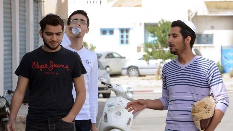 Des jeunes Juifs tunisiens discutent le 16 mai 2014 dans le quartier Hara Kbira de l'île tunisienne de Djerba, un site qui accueille un pèlerinage annuel (Crédit : : Fethi Belaid/AFP)