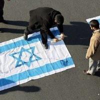 Illustration : des manifestants iraniens versent du kérosène sur le drapeau israélien pendant l'enterrement du général de brigade Mohammad Ali Allahdi, à Tehéran, le 21 janvier 2015. (Crédit : AFP/Atta Kenare)