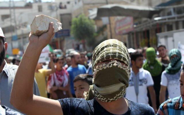 Un Palestinien, pierre à la main, à Hébron, le 18 septembre 2015. Illustration. (Crédit : Hazem Bader/AFP)