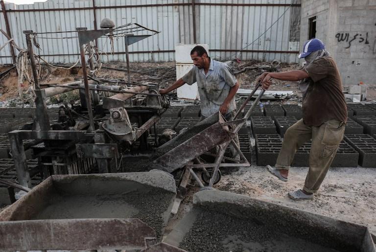 Ouvriers palestiniens dans une usine de ciment, pendant les quelques heures par jour d'électricité, au camp de réfugiés de Rafah, dans le sud de la bande de Gaza, le 24 septembre 2017. (Crédit : Said Khatib/AFP)