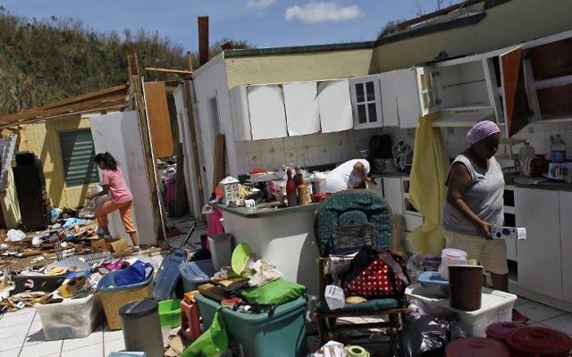 Les membres d'une famille collectent leurs affaires après la destruction par l'ouragan de leur maison à Toa Baja, à l'ouest de San Juan, à Puerto Rico,le 24 septembre 2017 après le passage de l'ouragan Maria (Crédit : AFP PHOTO / Ricardo ARDUENGO)