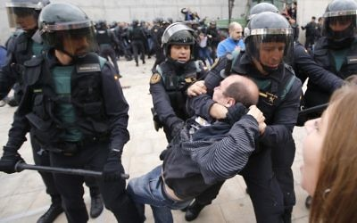 La Garde civile espagnole traîne un homme hors d'un bureau de vote à Sant Julia de Ramis, où devait voter le président catalan, le 1er octobre 2017. (Crédit : Raymond Roig/AFP)