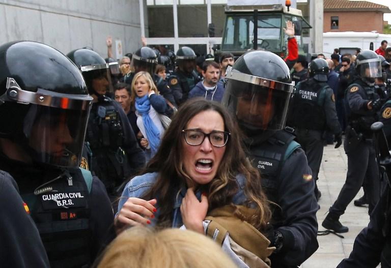 La Garde civile espagnole entoure une femme hors d'un bureau de vote à Sant Julia de Ramis, où devait voter le président catalan, le 1er octobre 2017. (Crédit : Raymond Roig/AFP)