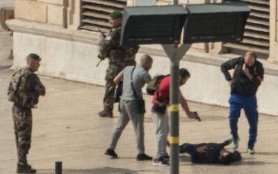 La police française pointe un pistolet sur un homme à terre, au centre, à la gare Saint-Charles de Marseille, en France, le 1er octobre 2017. (Crédit : Paul-Louis Leger/AFP)