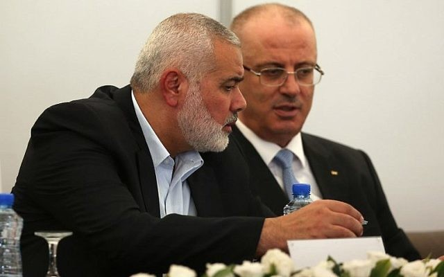 Ismail Haniyeh, à gauche, dirigeant du Hamas, et le Premier ministre de l'Autorité palestinienne Rami Hamdallah dans le bureau de Haniyeh, à Gaza Ville, le 3 octobre 2017. (Crédit : Mohammed Abed/AFP)
