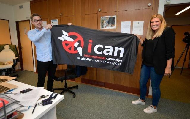 La directrice exécutive de l'ICAN, Beatrice Fihn (à droite) et le coordinateur Daniel Hogstan, tiennent une bannière avec le logo du groupe pour le désarmement nucléaire après que l'ICAN a remporté le prix Nobel de la paix pour sa campagne pour éliminer les armes nucléaires, le 6 octobre 2017, à Genève, Suisse (Crédit : AFP PHOTO / Fabrice COFFRINI)
