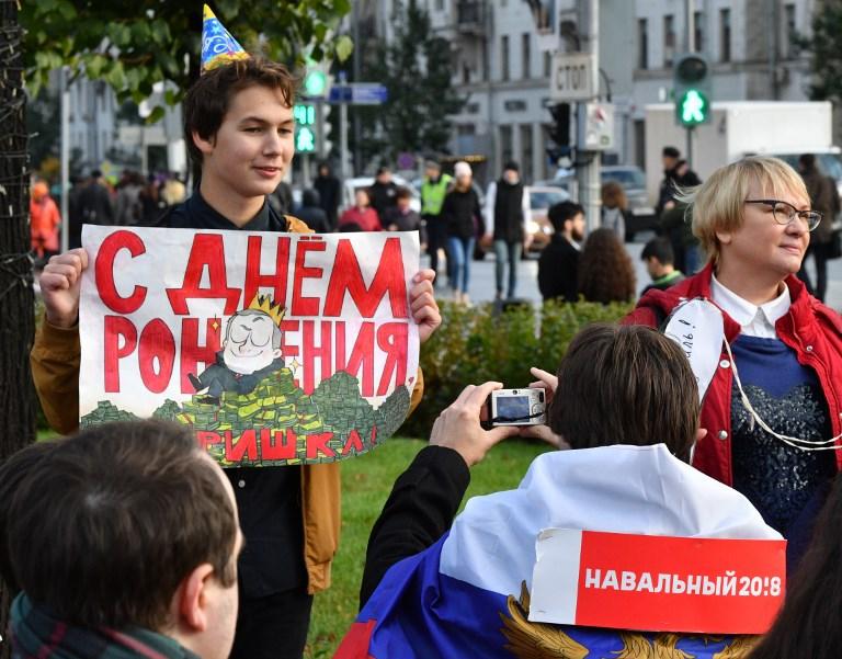 """Un manifestant souhaitant """"bon anniversaire, voleur"""" à Vladimir Poutine pendant une manifestation non autorisée, à Moscou, le 7 octobre 2017. (Crédit : Mladen Antonov/AFP)"""