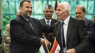 Saleh al-Arouri, à gauche, représentant du Hamas, et Azzam al-Ahmad, représentant du Fatah, après la signature d'un accord de réconciliation au Caire, le 12 octobre 2017. (Crédit : Khaled Desouki/AFP)