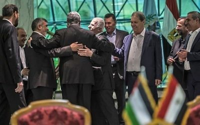 Khaled Fawzi, 3ème à gauche, chef des services égyptiens de renseignement, s'esclaffe aux côtés du leader du Hamas, Izzat al-Rishq, 2ème à gauche, et d'Azzam al-Ahmad du Fatah, au centre, suite à la signature de l'accord de réconciliation au Caire, le 12 octobre 2017 (Crédit :AFP / KHALED DESOUKI)
