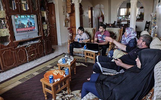 Des Palestiniens regardent à la télévision la signature d'un accord de réconciliation au Caire entre des factions palestiniennes rivales, le Hamas et le Fatah, le 12 octobre 2017 à Rafah, dans le sud de la bande de Gaza (Crédit : AFP / SAID KHATIB)