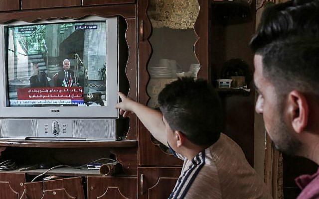 Les Palestiniens regardent à la télévision la signature d'un accord de réconciliation au Caire entre des factions palestiniennes rivales, le Hamas et le Fatah, le 12 octobre 2017 à Rafah, dans le sud de la bande de Gaza. (Crédit : Said Khatib / AFP)