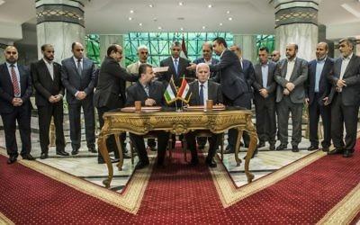 Saleh Arouri, assis à gauche, représentant du Hamas, et Azzam al-Ahmad, assis à droite, représentant du Fatah, pendant la signature d'un accord de réconciliation entre les factions palestiniennes rivales,  au Caire, le 12 octobre 2017. (Crédit : Khaled Desouki/AFP)