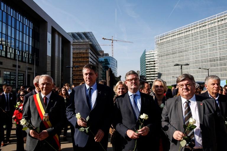 Jan Jambon, au centre à gauche, le ministre belge de l'Intérieur, et Julian King, au centre à droite, le secrétaire à la sécurité de l'Union européenne, roses blanches à la main, pendant une marche de soutien aux victimes du terrorisme et aux services de premier secours, à Bruxelles, le 18 octobre 2017. (Crédit : Dario Pignatelli/AFP)