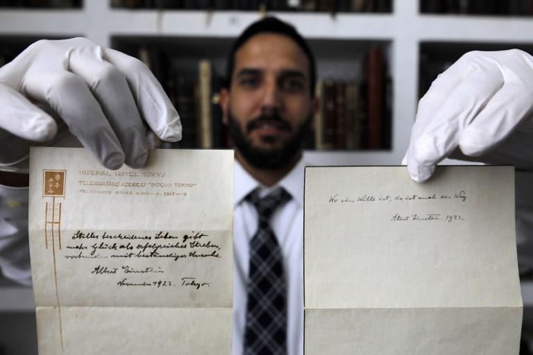 Gal Wiener, propriétaire gérant de la maison d'enchères Winner's de Jérusalem, présente deux notes écrites par Albert Einstein en 1922 sur le le papier de l'Imperial Hotel de Tokyo, le 19 octobre 2017. (Crédit : Menahem Kahana/AFP)