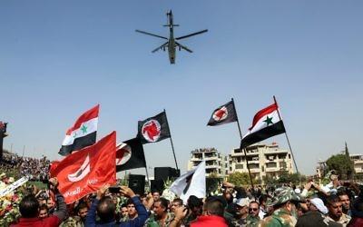 Des Syriens brandissent le drapeau national et celui du parti social nationaliste dans un stade au passage d'un hélicoptère russe Mil Mi-24 durant les funérailles du général de division Issam Zahreddine, dans la ville du sud de  Suwaida, le 20 octobre 2017 (Crédit :AFP /STRINGER)