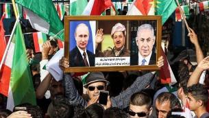 Un Kurde irakien avec des portraits du président russe Vladimir Poutine, à gauche, du Premier ministre israélien Benjamin Netanyahu, à droite, et du président du Kurdistan irakien Massoud Barzani pendant une manifestation devant les bureaux des Nations unies à Irbil, capitale de la région autonome, le 21 octobre 2017. (Crédit : Safin Hamed/AFP)