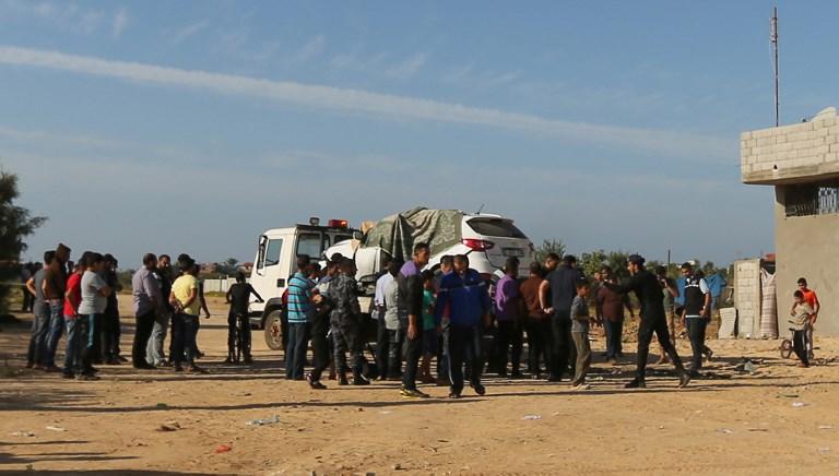 Forces de sécurité palestiniennes loyales au Hamas autour de la voiture du chef de la sécurité du groupe terroriste à Gaza, Tawfiq Abou Naim, qui a explosé dans le camp de réfugiés de Nusseirat, dans le centre de la bande de Gaza, le 27 octobre 2017. (Crédit : Mahmud Hams/AFP)