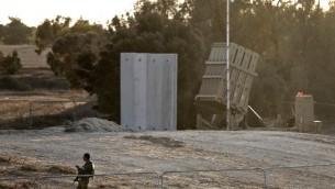Soldat israélien devant une batterie du Dôme de Fer déployé au niveau du kibboutz Kissufim, près de la frontière gazaouie, le 30 octobre 2017. (Crédit : Menahem Kahana/AFP)