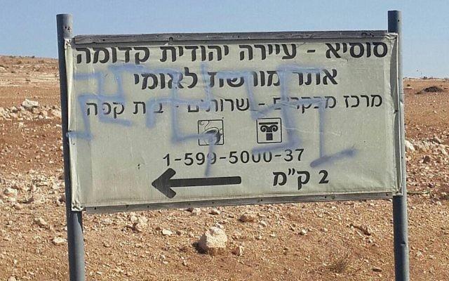 Croix gammées retrouvées sur le panneau d'un site archéologique devant l'implantation de Susya en Cisjordanie, en octobre 2017. (Crédit : conseil régional de Har Hebron)