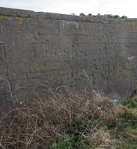 Un site d'exécution avec des trous laissés par les balles dans le mur sur l'île britannique d'Aurigny. (Crédit : Marcus Roberts)