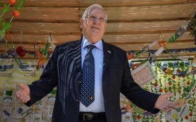 Le président Reuven Rivlin salue les visiteurs dans sa Soucca en 2016 et il refera la même chose cette année ainsi qu'à Tel Aviv (Crédit : Mark Neyman/GPO)