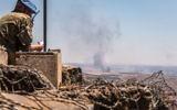 Un observateur de l'ONU installé à un poste de guet regarde la fumée qui s'élève d'un village syrien à proximité de la frontière israélo-syrienne dans les combats entre les rebelles et l'armée syrienne sur le plateau du Golan, le 25 juin 2017 (Crédit :Basel Awidat/Flash90)