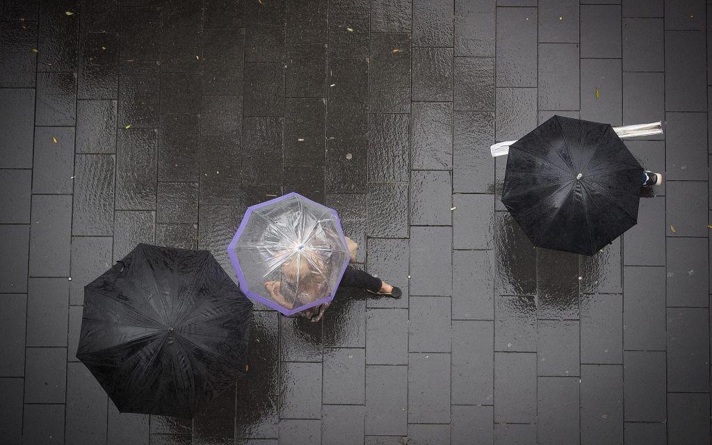 Des gens abrités sous leur parapluie dans le centre-ville de Jérusalem, le 9 octobre 2017 (Crédit : Yonatan Sindel/Flash90)
