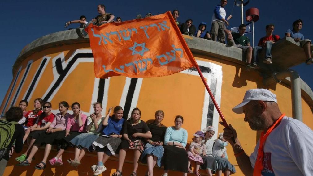 Des Israéliens sur le château d'eau de l'implantation évacuée de Homesh, le 12 juin 2007. (Crédit : Maya Levin/Flash90)