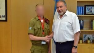 Le ministre de la Défense Avigdor Liberman serre la main d'un soldat de l'armée israélienne qui avait tiré et blessé un terroriste meurtrier de trois Israéliens dans l'implantation de Halamish, le 21 juillet 2017 (Crédit : ministère de la Défense)