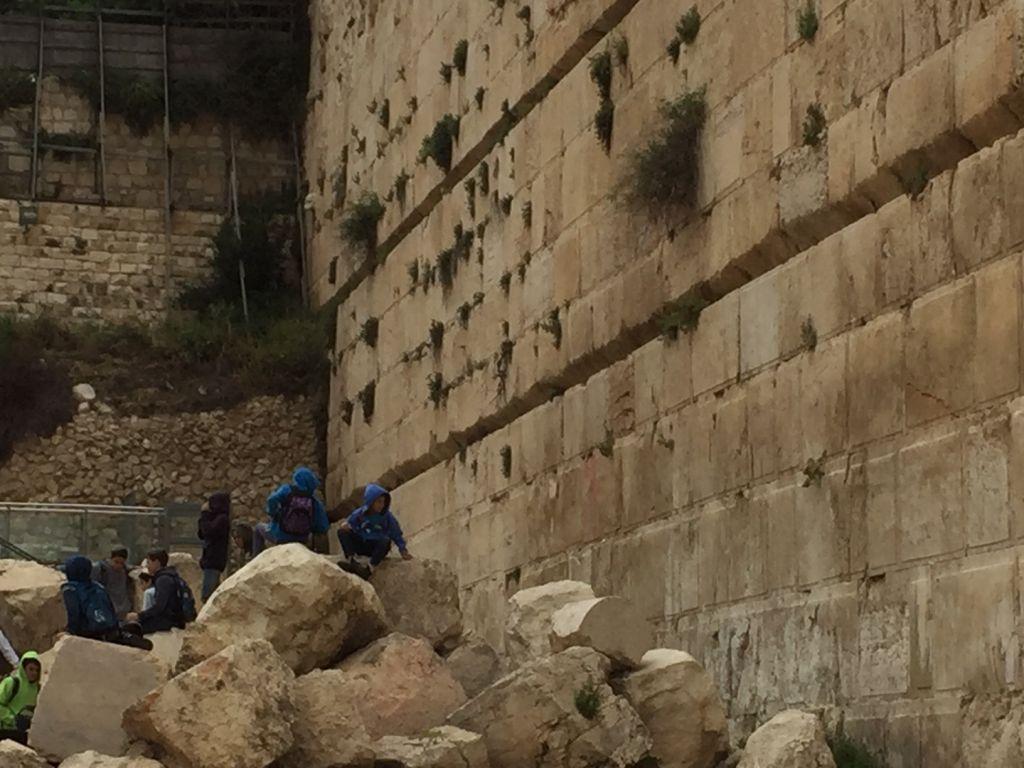 Des enfants jouent sur les pierres âgées de 2000 ans du parc archéologique Davidson de la Vieille Ville de Jérusalem, le 12 avril 2016. (Crédit : Amanda Borschel-Dan/Times of Israël)
