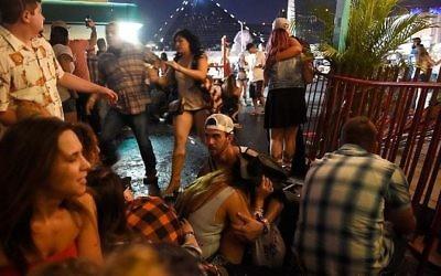 Les gens se mettent à l'abri au festival de musique country après avoir entendu des coups de feu, à Las Vegas, dans le Nevada, le 1er octobre 2017. (Crédit : David Becker/Getty Images/AFP)