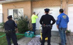 Nettoyage d'une croix gammée sur la porte d'un garage d'une maison de Staten Island, en octobre 2017. (Crédit : NYPD 23rd Precinct via JTA)