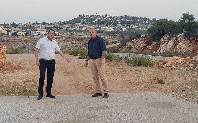 Le président du Conseil régional de Samarie, Yossi Dagan, à gauche, et le président du conseil local de Beit Arye, Avi Naim, montrent une route de contournement en Cisjordanie encore inachevée, des années après le début de sa construction (Crédit : Autorisation Roy Hadi)