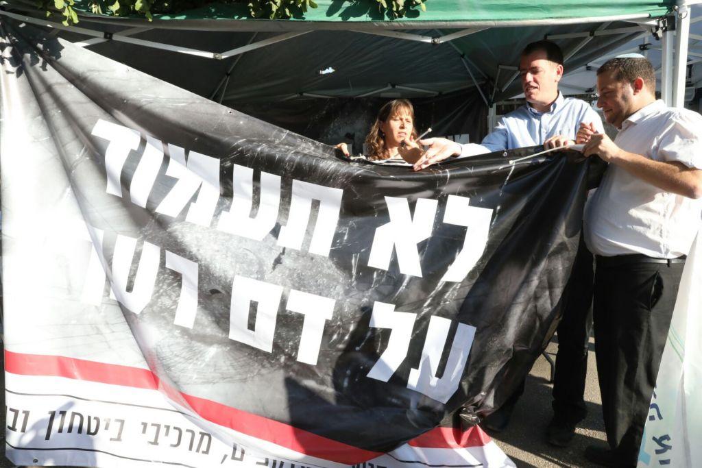 """Yossi Dagan, à droite,président du Conseil régional de Samarie, avec la bannière """"Tu ne t'élèveras pas contre le sang de ton prochain"""" devant une tente de protestation des dirigeants des implantations devant la résidence du Premier ministre, à Jérusalem, le 24 octobre 2017. (Crédit : autorisation de Miri Tzachi)"""