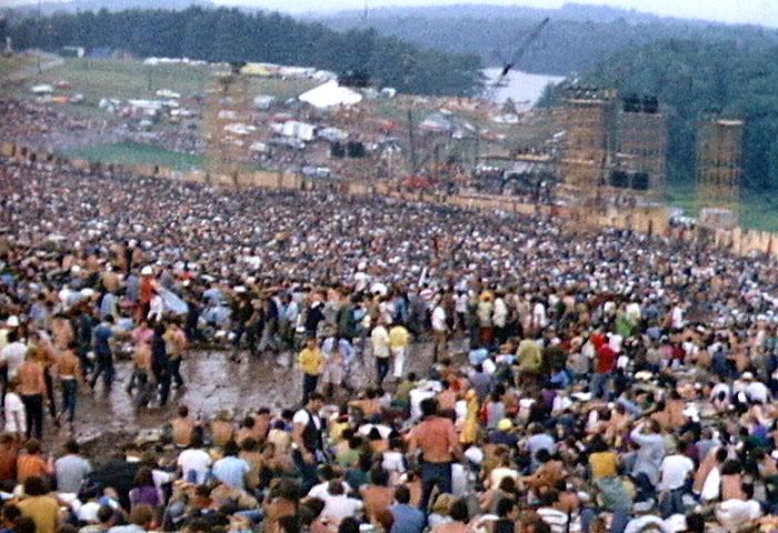 La foule participant au festival de Woodstock remplit un amphithéâtre avec la scène au fond, en août 1969 (Crédit : Derek Redmond et Paul Campbell / CCA-SA 3.0)