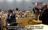 Bassem Eid, à droite, tente de parler pendant qu'un perturbateur est repoussé de la scène après avoir tenté de l'agresser dans une synagogue de New York, le 26 octobre 2017. (Crédit : capture d'écran Deuxième chaîne)