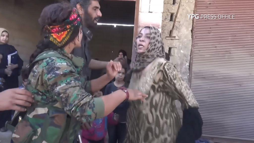 Une femme arrache les vêtements noirs imposés par l'Etat islamique pour célébrer la libération de Raqqa, le 13 octobre 2017. (Crédit : capture d'écran YouTube/YPG)