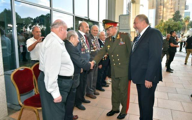 Le ministre de la Défense Avigdor Liberman, à droite, et son homologue russe Sergueï Choïgou, avec des vétérans de l'armée israélienne à la Kirya, à Tel Aviv, le 16 octobre 2017. (Crédit : Ariel Hermoni/ministère de la Défense)