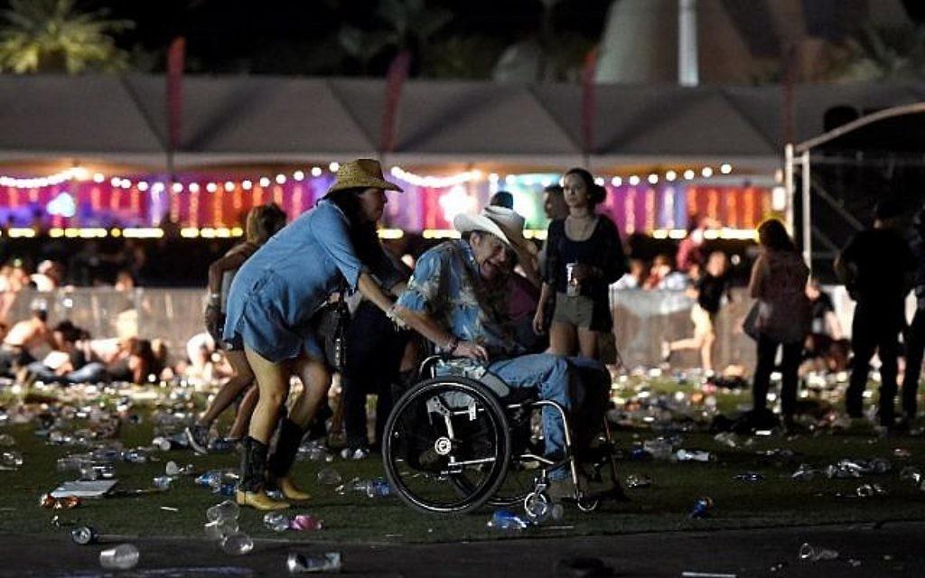 Un homme en chaise roulante est conduit vers la sortie du festival Route 91 Harvest, après des coups de feu, à Las Vegas, dans le Nevada, le 1er octobre 2017. (Crédit : David Becker/Getty Images/AFP)