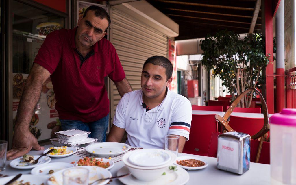 Saleem Sharif, l'un des seuls Arabes israéliens aveugles qui utilise un chien-guide, dans un restaurant de Nazareth. Lorsqu'il a amené pour la première fois son chien, Winston, il n'a pas été autorisé à l'amener dans des restaurants de la région, mais les attitudes changent lentement (Crédit : Luke Tress / Times of Israel)