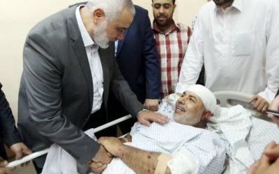 Ismail Haniyeh, le chef du Hamas, au chevet de Tawfiq Abou Naim à l'hôpital Shifa de Gaza Ville, dans la bande de Gaza, le 27 octobre 2017. (Crédit : Mohammad Austaz/Hamas)