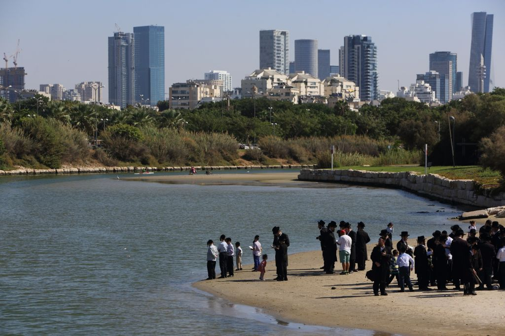 Les Juifs prient sur les rives du fleuve Yarkon à Tel Aviv, le 28 septembre 2017, pour le rituel de Tashlich, durant lequel les pratiquants jettent symboliquement leurs péchés dans l'eau (Crédit : Yaakov Naumi/Flash90)