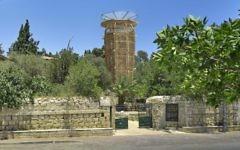 La sculpture en sabra qui représente une tour créée par l'architecte Martin Rajnis émerge des jardins verdoyants de la maison Hansen à Jérusalem (Autorisation : Maison  Hansen)