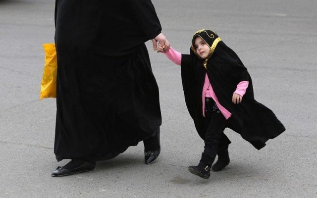 Illustration. Une maman marche avec sa fille en Irak (Crédit : AFP/AHMAD AL-RUBAYE)