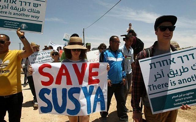 3 Palestiniens, des étrangers et des pacifistes israéliens manifestent dans le village de Sussiya au sud de la Cisjordanie contre la démolition du village palestinien dans les collines d'Hébron, le 5 juin 2015. (AFP / Hazem Bader)